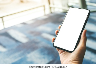 Mockup image of a woman's hands holding and using black mobile phone with blank screen while sitting in the airport