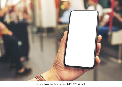 Mockup image of woman's hands holding black mobile phone with blank screen in subway