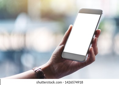 Mockup image of woman's hands holding white mobile phone with blank screen