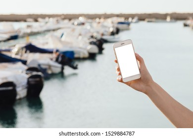 Mockup image of woman's hands holding white mobile phone with blank screen on blurred background of port with yachts