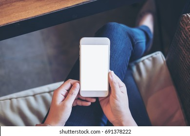 Mockup image of woman's hands holding white mobile phone with blank screen on thigh in office