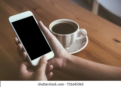 Mockup image of woman's hands holding white mobile phone with blank black screen and white coffee cups in modern loft cafe