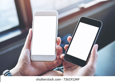 Mockup image of a woman's hands holding two mobile phones with blank white screen in modern cafe