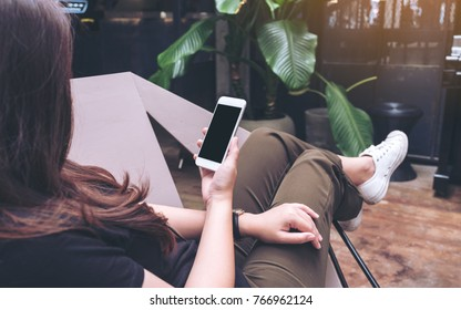 Mockup image of woman's hands holding white mobile phone with blank black screen on thigh while sitting and chilling in modern cafe