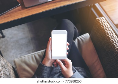 Mockup image of a woman's hands holding white mobile phone with blank white screen on thigh