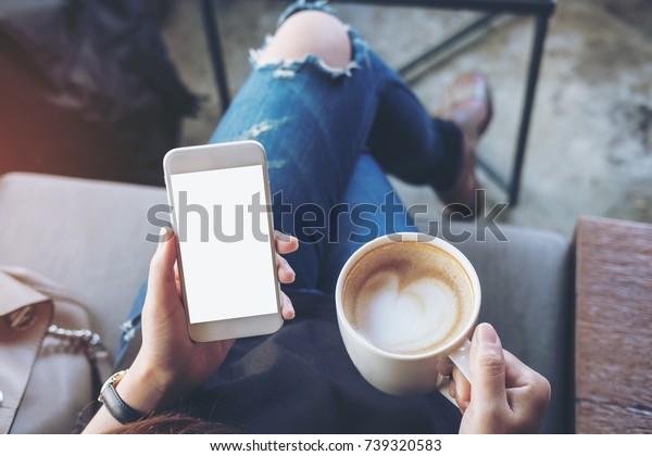 白い携帯電話を持つ女性の手のモックアップ画像で、太ももにスクリーン、カフェのコーヒーカップ