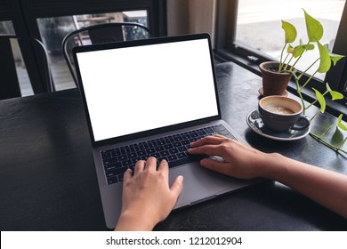 Mockup image of a woman's hands using and typing on laptop with blank white desktop screen with coffee cup on wooden table in cafe