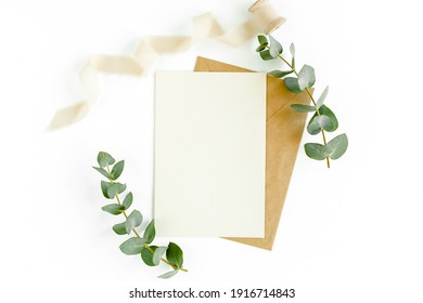 Mockup invitation, blank greeting card and green leaves eucalyptus. Flat lay, top view.