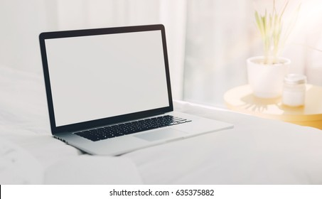 Mock-up of laptop with blank white screen on bed, Workplace fashion blogger early in the morning, Sunrise, Shallow DOF.