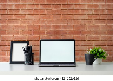 Mockup laptop computer, photo frame,  coffee and plant decoration on office table and brick wall background.