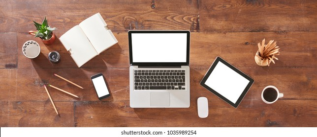 mock-up of laptop, digital tablet and smartphone, top view on a desktop. All technological tool on the old wood table isolated white screen