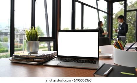 Mockup laptop and document paper on business table in meeting room.