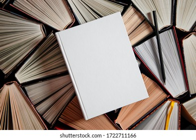 Mockup layout and a black pencil lie on multicolored open books