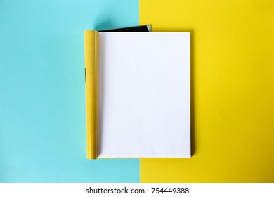 Mock-up magazine and catalog concept. Top view. Open page of the magazine on a blue and yellow background. Copy space. Template