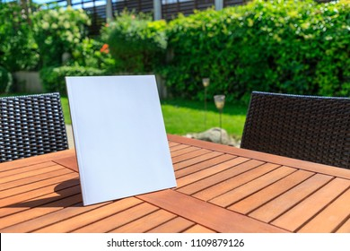 Mockup of a magazine cover on a wooden table in the garden in summer.