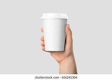 Mockup of male hand holding a Coffee paper cup isolated on light grey background