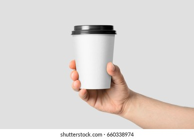 Mockup of male hand holding a Coffee paper cup isolated on light grey background.
