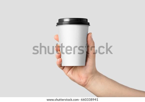 Händlerin, die eine Kaffeepapiertasse hält einzeln auf hellgrauem Hintergrund.