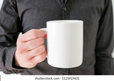 Mockup of a man with black shirt holding coffee mug in his right hand