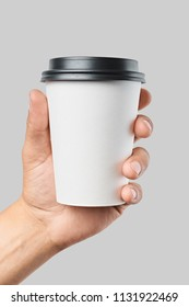 Mockup of men's hand holding white paper mid size cup with black cover isolated on grey background