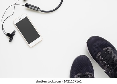Mockup mobile cellphone with wireless bluetooth earphone and running shoes on white background. Healthy active lifestyles background concept. Daily workout and relax music lifestyles .
