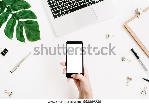 Mockup of mobile phone with blank copy space screen in female hand. Flat lay, top view workspace