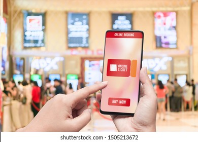 Mockup mobile phone hand using smartphone to buy cinema tickets with blurred image of ticket sales counter at movie theater with graphic icon, online booking and payment concept