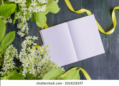 Mockup notebook with white spring flowers and rustic wooden background empty space for your text, top view