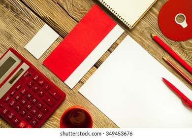 The mockup on wooden background with red calculator, pen, pencil, cup of coffee, white blank paper for writing, notebook and disk