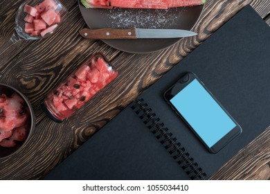 Mockup of open black menu and smartphone with watermelon slices around. Display clipping path.