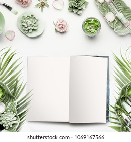 Mock-up of open magazine or catalog for beauty and cosmetic products. Modern natural skin care equipment with roses, succulents, facial mist water spray and green tropical leaves on white background