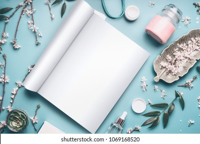 Mock-up of open magazine or catalog for beauty and cosmetic products on pastel blue desktop with twigs and cherry blossom. Modern spring skin care concept, top view, flat lay