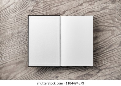 Mockup of opened blank book on vintage wood table background. Flat lay.