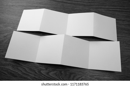 Mockup of opened four fold brochure at wooden background