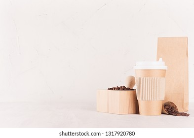 Mockup packing for coffee products and shop - brown paper cup, packet and mortar with coffee beans on white wood table, copy space, copy space.