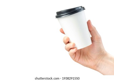 Mockup of paper coffee cup in hand isolated on white background. Male hand holds a disposable mug with a black lid. Advertising latte or tea.