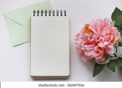 Mockup photography with pink peony, notebook and envelope. Desktop workplace designer, artist, painter top view. Modern trend template for advertising.