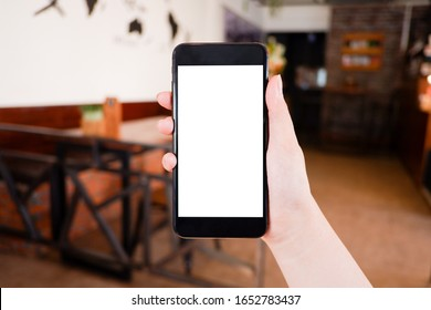 Mockup picture of business woman's hands holding smart phone with white blank screen in modern place.