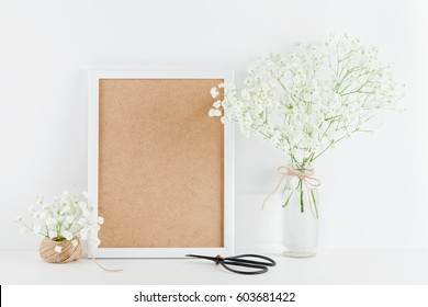 Mockup of picture frame decorated gypsophila flowers in vase on white working desk with clean space for text and design your blogging.