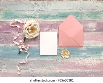 Mockup of the piece of paper with iridescent flower on wooden background