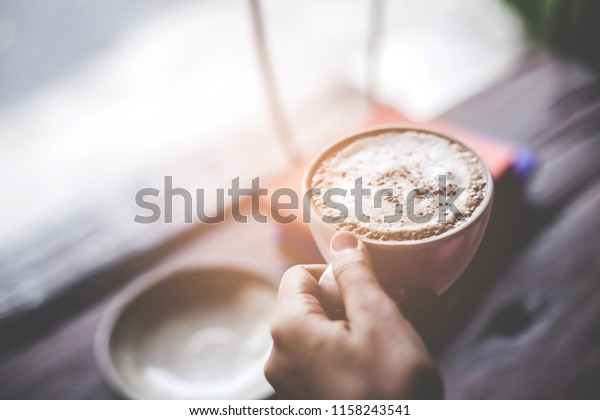 Mockup portrait of a woman hand holding cup of cappuccino or latte coffee with a foam white on a wooden background in a cafe. Colorful books stacked on the table.