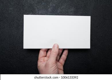 Mockup of a postal envelope in hand on a black background.