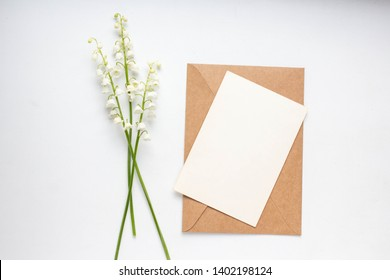 Mockup with postcard and lilies of the valley on white background card and lilies of the valley