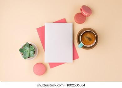 Mockup with postcard, sweets and cup of coffee on beige background. Pink envelope with empty card and green plant. Flat lay, top view.