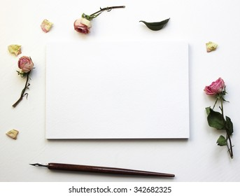 Mockup for presentations with dry roses. Desktop workplace designer, artist, painter top view. Modern trend template for advertising.