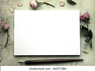 Mockup for presentations with dry roses. Vintage background. Desktop workplace designer, artist, painter top view. Modern trend template for advertising.