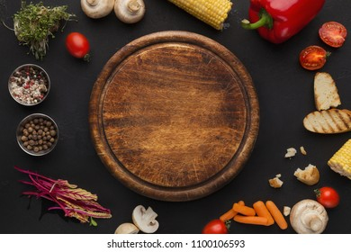 Mockup for recipe or masterclass advertising. Empty wooden cutting board and cooking ingredients on black background, top view, copy space