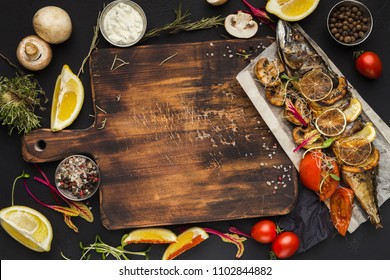 Mockup for recipe or masterclass advertising. Grilled fish, raw vegetables and spices framing wooden cutting board, top view, copy space
