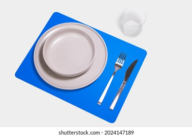 mockup rectangular pvc placemat with plate, fork and knife. white background on blue placemat