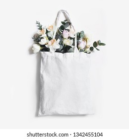 Mock-up scene of blank shopping canvas tote bag with pink tulips, daffodils flowers and eucalyptus  isolated on white backfound. Spring, Easter sale. Eco friendly and zero waste concept. Flat lay.
